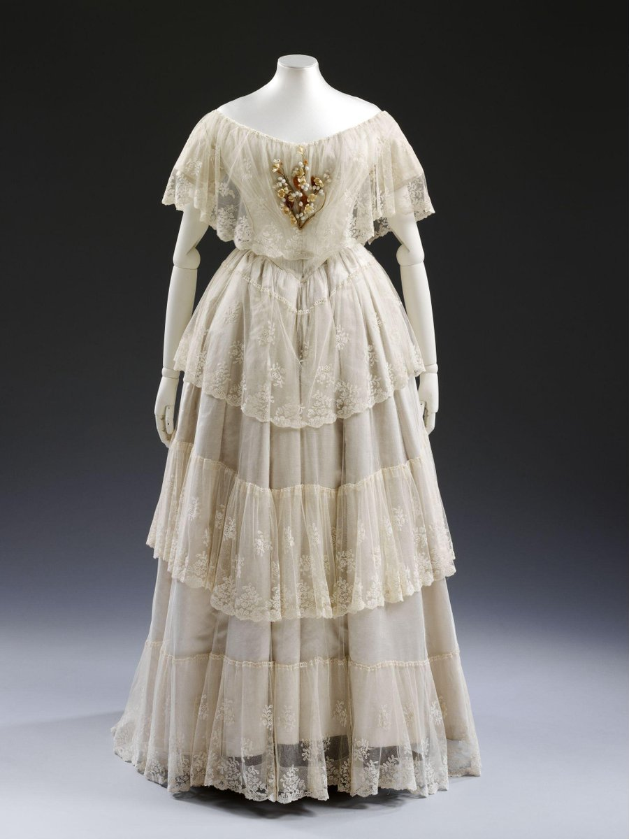 (c)Victoria and Albert Museum, London - White silk satin wedding dress with overdress of embroidered flounced net lace, white satin bonnet, a bonnet-veil of applied bobbin lace motifs on net, a handkerchief of white embroidered cambric, a pair of garters of fine canvas embroidered with rosebuds, and a fan with a leaf of Brussels lace initialled H.B. (for Henrietta Bell) on mother of pearl sticks