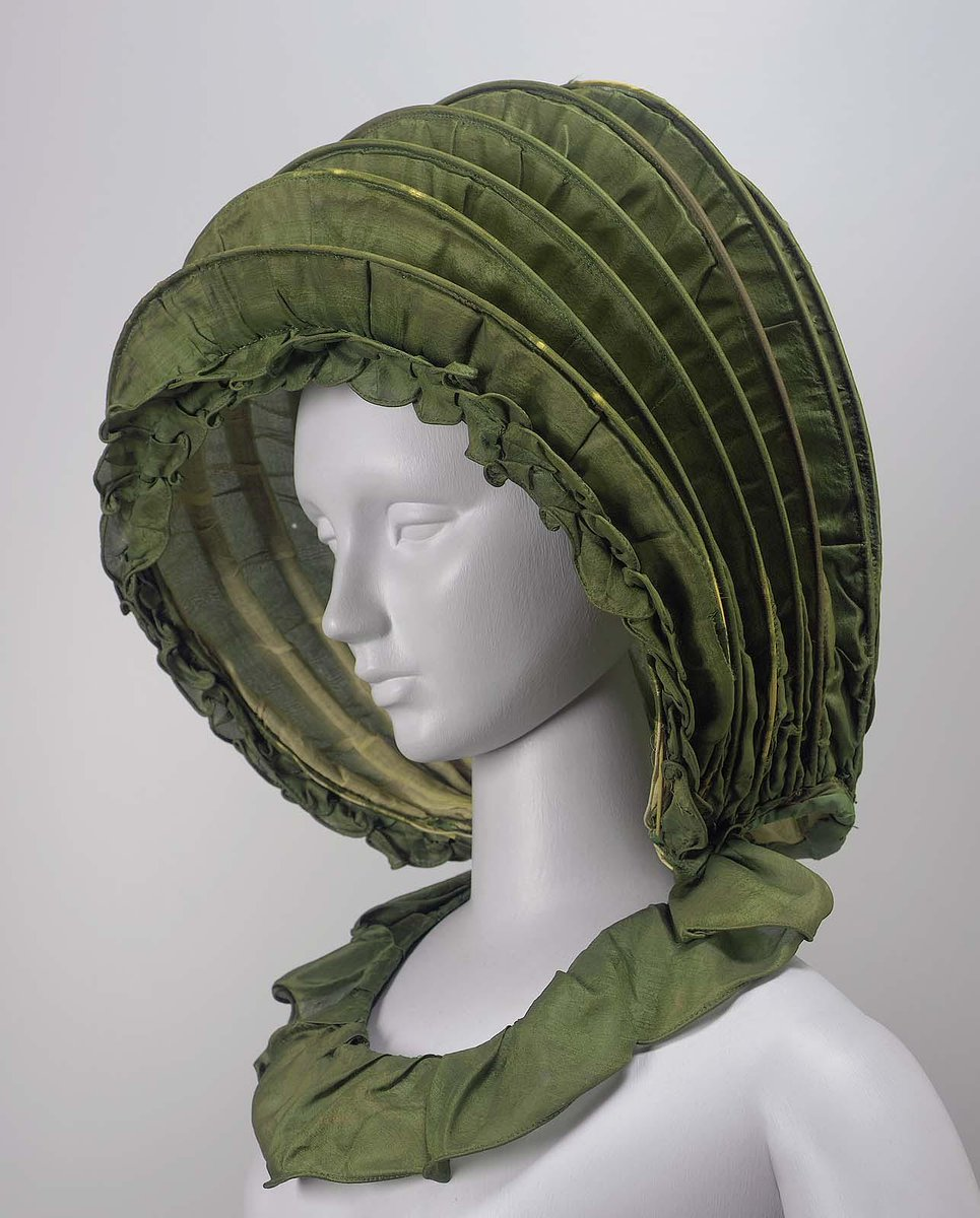 Silk, cane and wire, linen lining - a very fun green hat made out of caning on green fabric concentric circles. Almost like a covered wagon on someone's head. From the Boston MFA.
