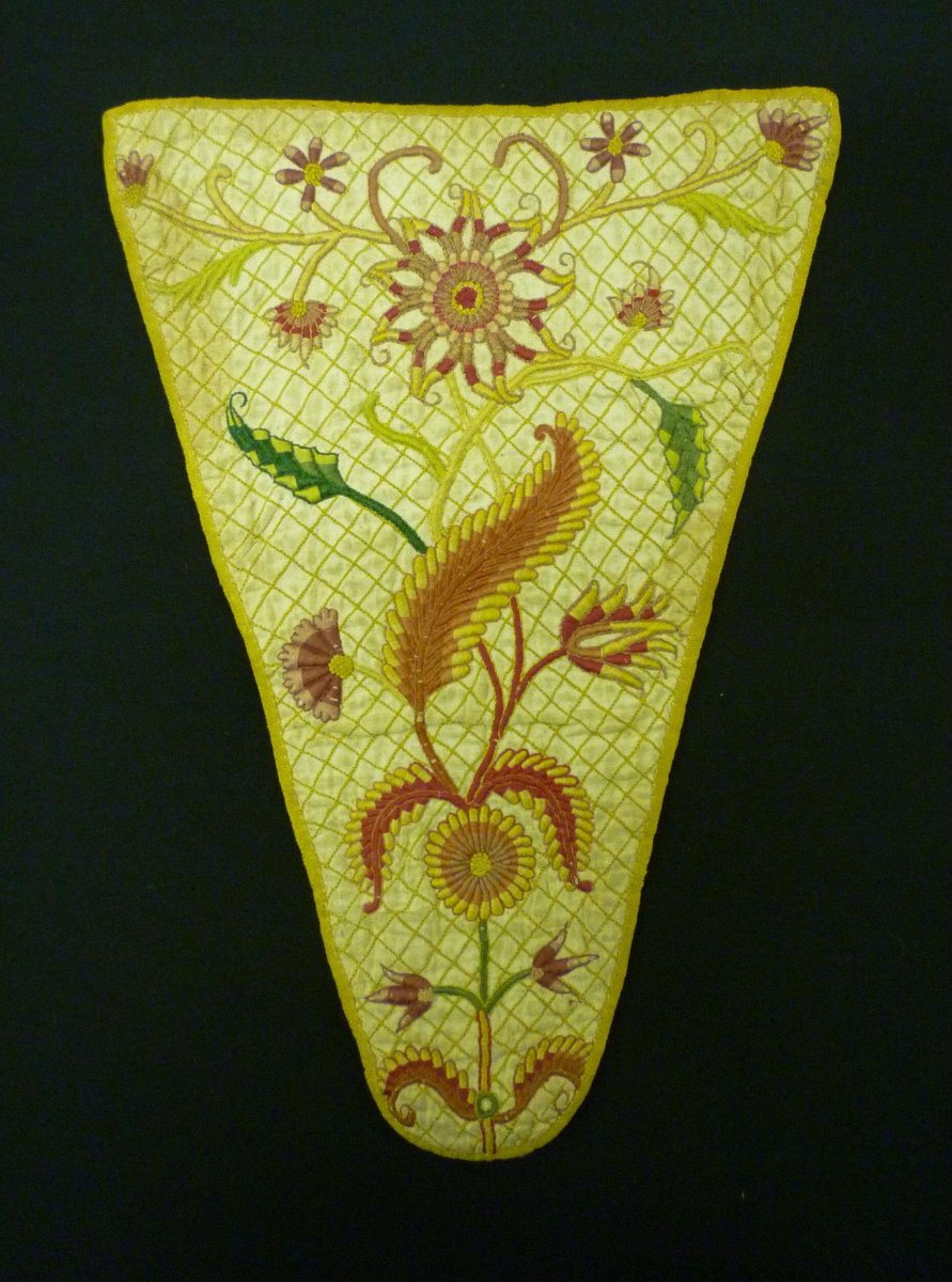 ©Victoria & Albert Museum, London - Woman's stomacher of bleached linen, backed with coarse linen, lined with a finer linen and reinforced with strips of baleen. It is embroidered with coloured silks in stem and satin stitches and French knots in a single branching stem, bearing exotic flowers and leaves, against a ground of back-stitched diaper pattern. The edges are bound with narrow yellow silk grosgrain ribbon.  There are two pins, one loose headed and the other solid headed, underneath the lining.