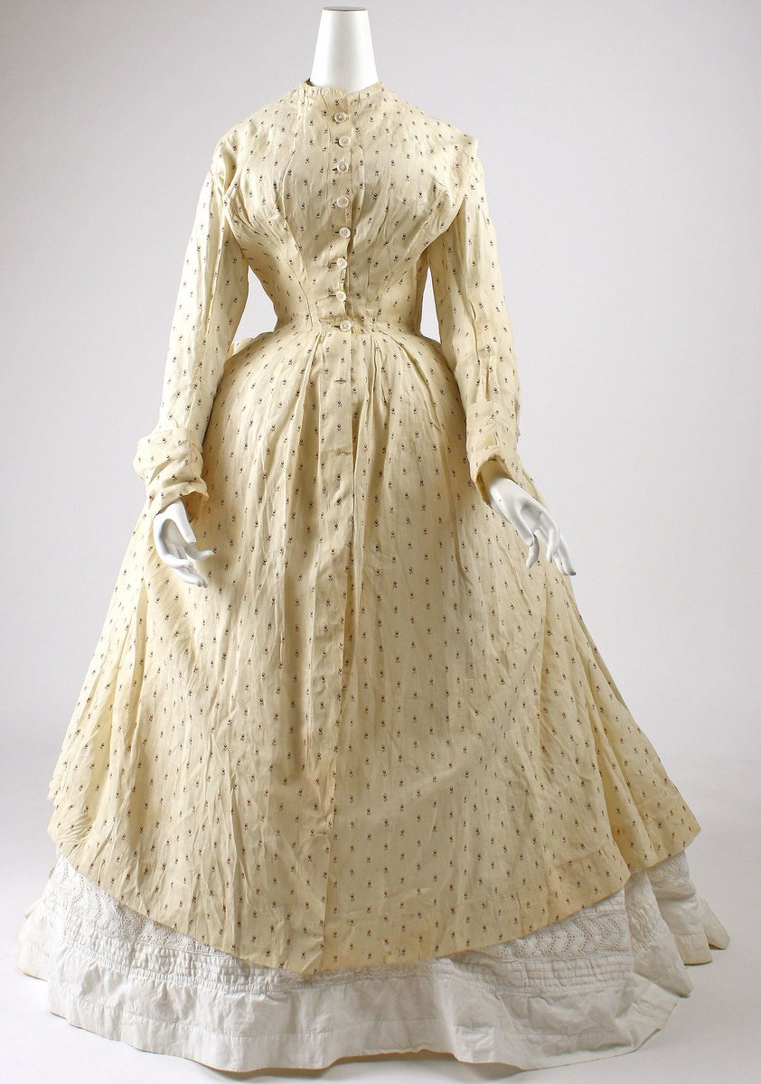 A Robe à la Polonaise, American, in two pieces -- an overdress, and an underdress. It has a high collar, and long sleeves. The overdress has a print of tulips and is beige. The underdress is white. It has a narrow waist and buttons all the way down. The bodice has pleating at the chest.