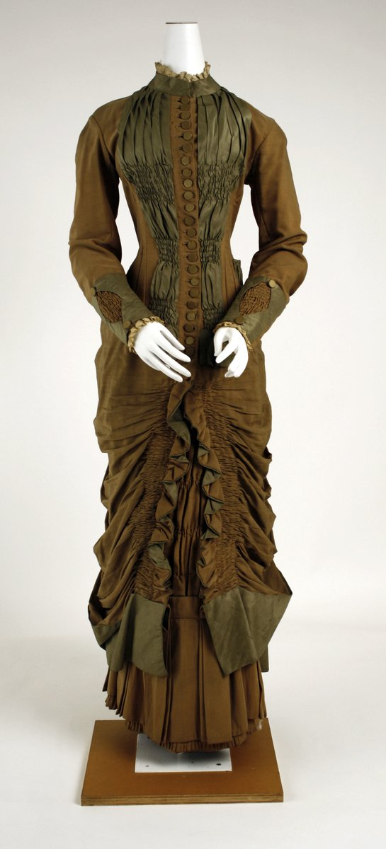 Princess line, Ruched ochre and chartreuse silk gown with high collar, long sleeves, and lots of draping. Very narrow, pleating at bottom. Wool and silk.