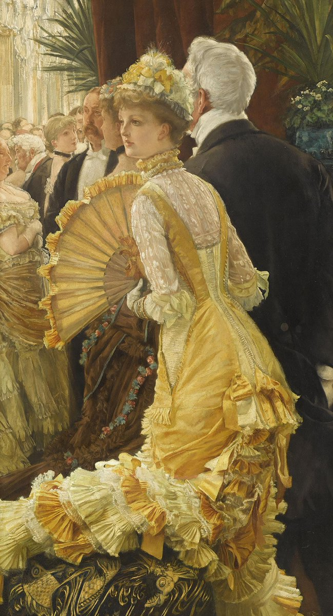 A woman in a yellow dress, princess line (no big bustle), with lots of folds, and an enormous fan. Her hair is up with ribbons, and her sleeves and neckline are long. There are men in the background and a woman as well, but she seems otherwise alone.