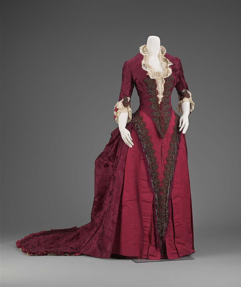 Dark purplish red silk with tulip figure; bodice with long V in lower center front, elbow-length sleeves, peplum tabs lower center back, neck and sleeves trimmed with ruffles and lace, front and sleeves trimmed with repeat of cone motif in dark colored beads and metal braid; skirt center front panel of red ribbed silk with same embroidery as bodice and red silk and colored bead fringe; most of fullness of skirt and soft pleats and puff center back, train edged with dark red silk pleated ruffle. Boston MFA, public domain.