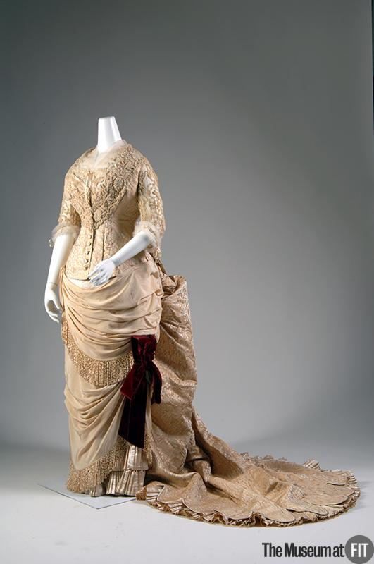 Yellow silk brocade, cream silk crepe, silk net, chenille, magenta silk velvet, glass faux pearls, and seed beads - another classic Worth shape, with that snatched waist -- this time with a long train. From the Museum at FIT.