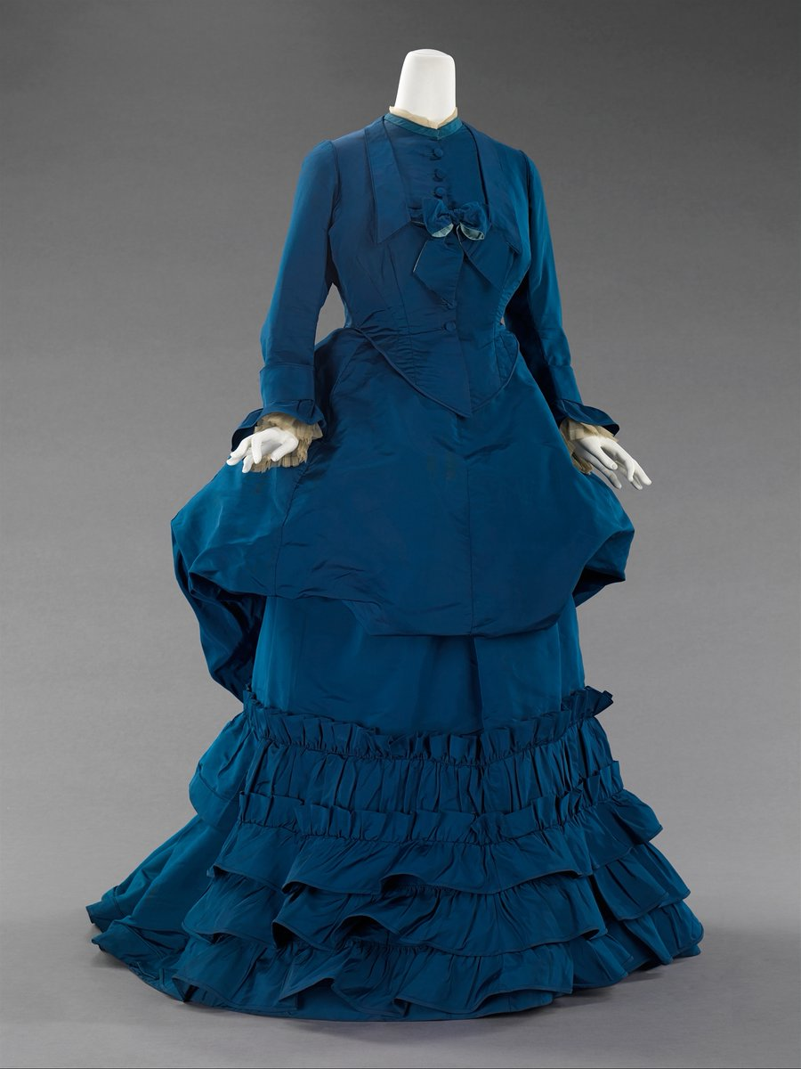 This one is hard to explain because it's like a two-tier dress. Like a goblet turned upside down. It's deep blue, and is similar to shape -- that almost suit shape -- but then it has a blobby droop? And then lots of pleats and ruffles. Met Museum, public domain.