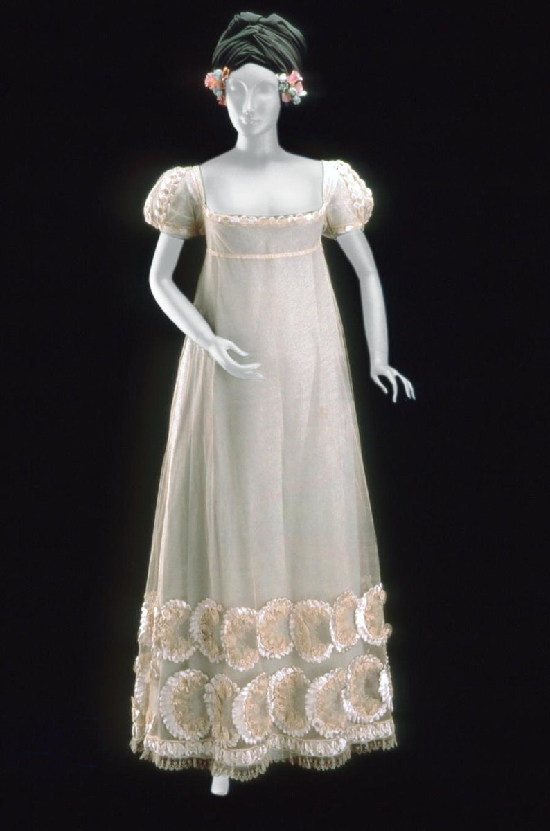 White, high waisted tulle dress with short, puffed sleeves, low, square neckline, and drawstring closure which ties at back; trimmed with four bands of blue-white satin, tulle, and cream silk cord (single band of same trim at neckline and cuffs). Wide decorative border at hem; two rows of satin loops formed into crescent shapes with silk cording, tulle rosettes, and cream silk embroidered with three-lobed leaves; single continuous band of rouched ribbon between two rows of cording; scalloped net at hemline embroidered with three-lobed leaves, (white satin slip not original, see inscription) - Boston MFA, public Domain