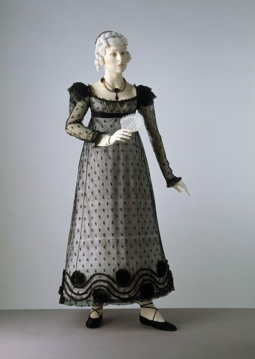 ©Victoria and Albert Museum, London - The dress is trimmed at the hem with padded black satin rouleaux and rosettes. The bodice has a low, square neck and fastens at the back with tapes. It is very short-waisted with slight fullness eased in at the front. The gored skirt is attached smoothly except for a wide panel of tight gathering at the back. The epaulettes are wired and, like the cuffs on the long sleeves, made from satin with an applied cord decoration.