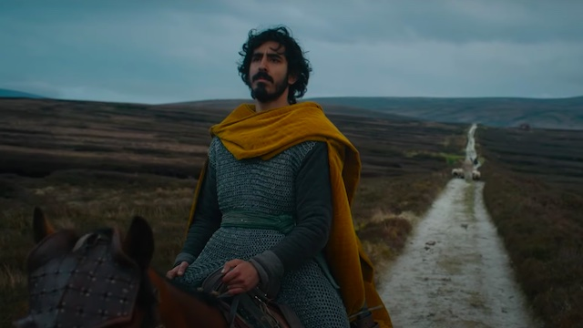 Dev Patel as Sir Gawain in the Green Knight from A24 films. On horseback at the beginning of his adventure, a white lime road behind him, staring out. He wears chain mail and the same yellow cloak.