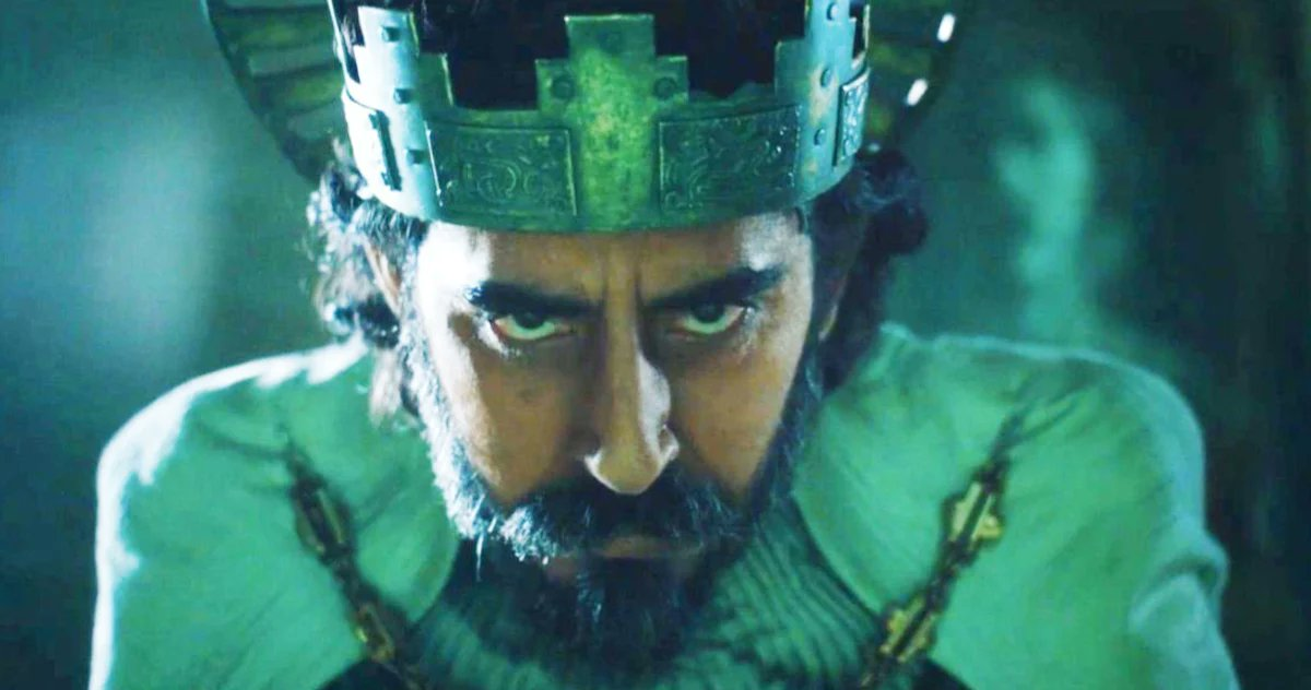 Angry looking Dev Patel, cast in green.