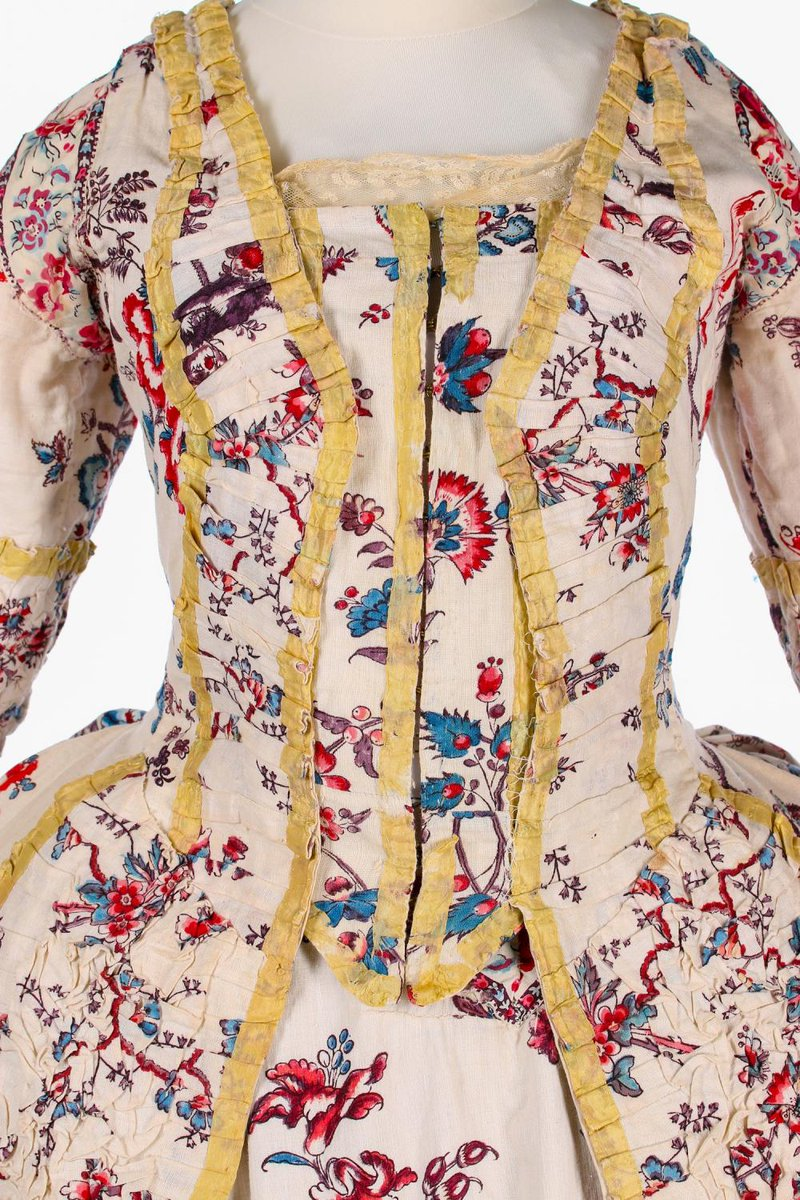 More chintz. A printed cotton 'Indienne' robe à la Française, French, 1770s, boldly printed with large scale flowering boughs, in shades of blue, red and brown, edged in ivory silk ribbon; the open robe with ruffled, gathered, curved cuffs, closed-front 'stomacher' inner panels with hook and eye closure, matching ruffled graduated bands to the front skirt closure and petticoat front, pocket slits to each hip, the dress with shot blue-pink silk lining; the matching petticoat of heavy coarse cotton applied to the front and rear lower skirt with Indienne chintz; together with a pair of late 19th century panniers (4) - From invaluable.com