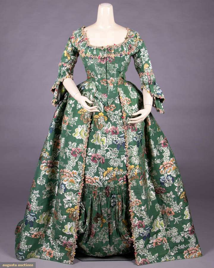 """Open robe of Spitalfields silk w/ fitted back construction a l'Anglaise, CF hook & eye closure edged w/ passementerie & silk flowers to pleated décolleté, elbows, double engageante sleeves & to CF skirt opening, petticoat front w/ deep double draped & peated furbelows w/ gathered & pleated band to upper edge, entirely constructed of Spitalfields silk brocaded broché, point de rentrée, twill design on tabby ground, c. 1736, textile dimensions: WD 19.75, length of repeat 23"""", selvage Wd 0.25"""", (CF bodice altered in the 19th C, 2.5""""repair/shattering at left W, petticoat: few tiny-0.25"""" worn spots throughout, modern W band, 5.5"""" split above furbelow, 3.5"""" & 2.5"""" splits above hem) -  SPITALFIELDS SILK OPEN ROBE & PETTICOAT, COLONIAL, 1750-1760  - Augusta Auctions"""