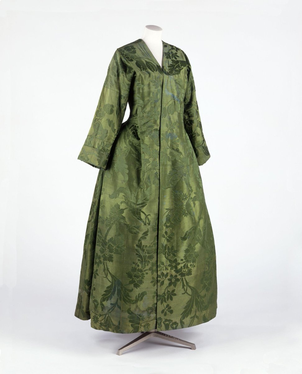 ©Victoria and Albert Museum, London -  Woman's banyan of green silk damask in a large pattern of leaves and flowers, lined with dark green silk sarsenet. The banyan is extensively pieced with no complete repeat of the damask pattern. It is T-shaped in cut, open at the front, with sleeves reaching to the forearm with a turn-back cuff. There is 1 pleat on either side of the front and 1 tapered box pleat at the centre back.    The piecing and signs of fomer folds and pleats suggest a previous garment. It was possibly then pieced into a man's T-shaped night gown and reconfigured again for a woman with shaping at the torso and shoulders and addition of a linen lining above the waist.