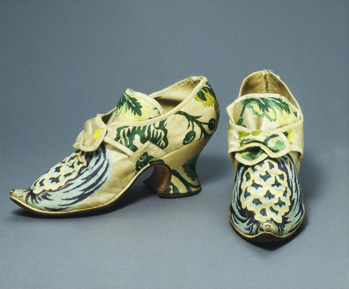 ©Victoria and Albert Museum, London - Pair of woman's shoes made of white brocaded silk with a design in shades of blue, pink and green. The upper and heel are covered with the same material. They are bound with white grosgrain ribbon and the uppers are lined with white leather. The inner sole is made of brown leather. The buckles are made of polished steel. There is a white leather lining between the sole and the shoe. The shoes feature a design of large fruit placed over the toes.