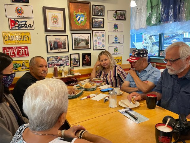 Michelle, masked, enjoys a meal with Jaime Rodriguez and four Boston residents. Colorful photos and old license places decorate the wall behind them.