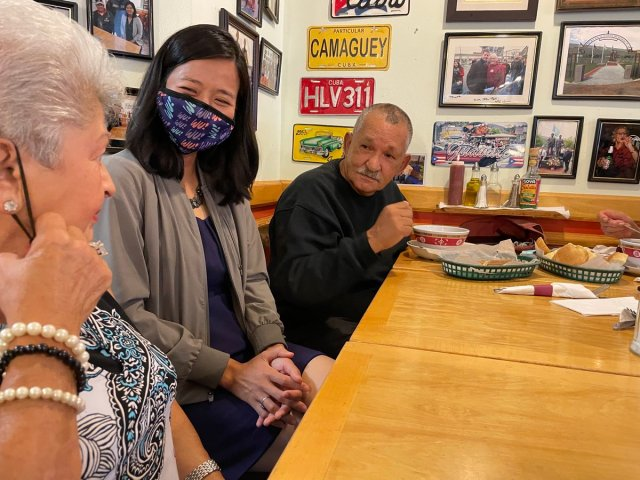 Michelle, masked, enjoys a meal with Jaime Rodriguez and a Boston resident. Colorful photos and old license places decorate the wall behind them.