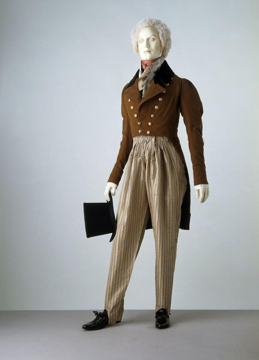 ©Victoria and Albert Museum, London - These trousers are cut full at the thigh and taper to the ankles. Buttoned straps under the instep keep the fabric from riding up. The fullness at the hip is evenly gathered to the front of the waistband. Cossack trousers were introduced to Britain in 1814 when Tsar Aleksandr I travelled to London from Russia for the peace celebrations that followed Napoleon Bonaparte's abdication in April of that year. The Cossack soldiers in Aleksandr's entourage wore a similar style of trousers, which soon became fashionable in Europe. A brown jacket and top hat and neck scarf finish the ensemble.