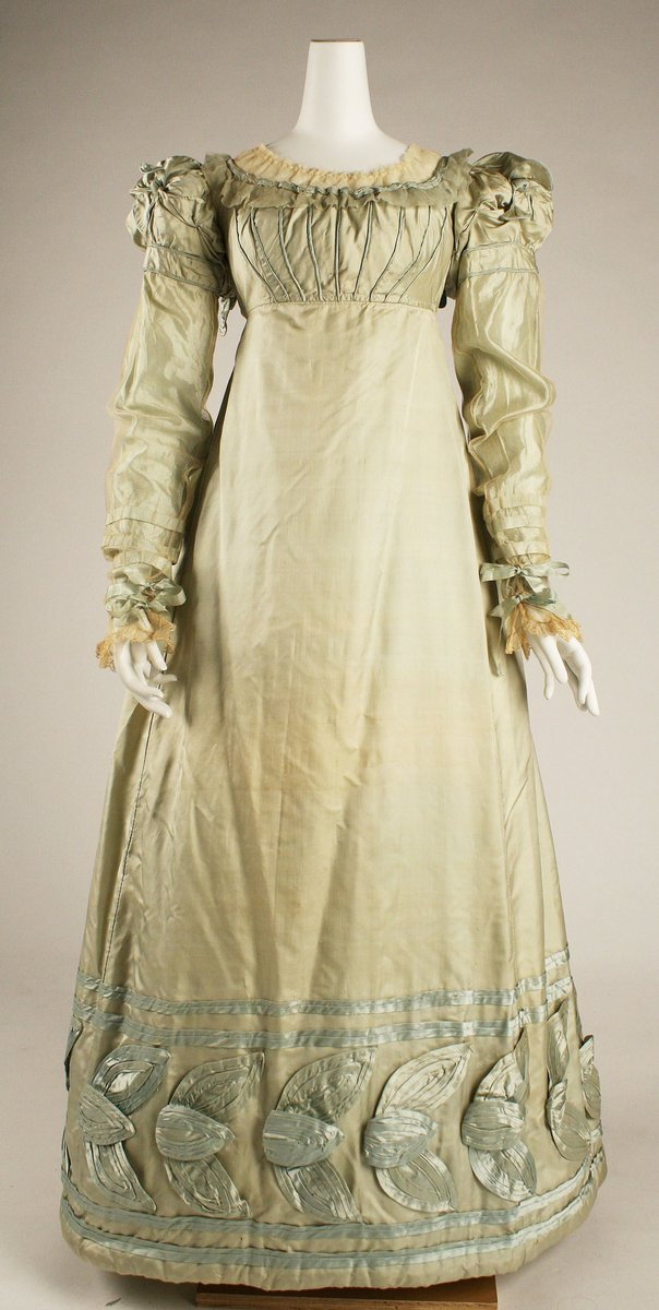 A dress that seems to step out of a Jane Austen novel combines the champagne-light coloring of spring with cream netting that buttresses décolletage and sheathes the sleeves. Similarly, abstracted leaf forms at hem and neckline make a subdued version, suitable to the Regency epoch, of a floral transfiguration.