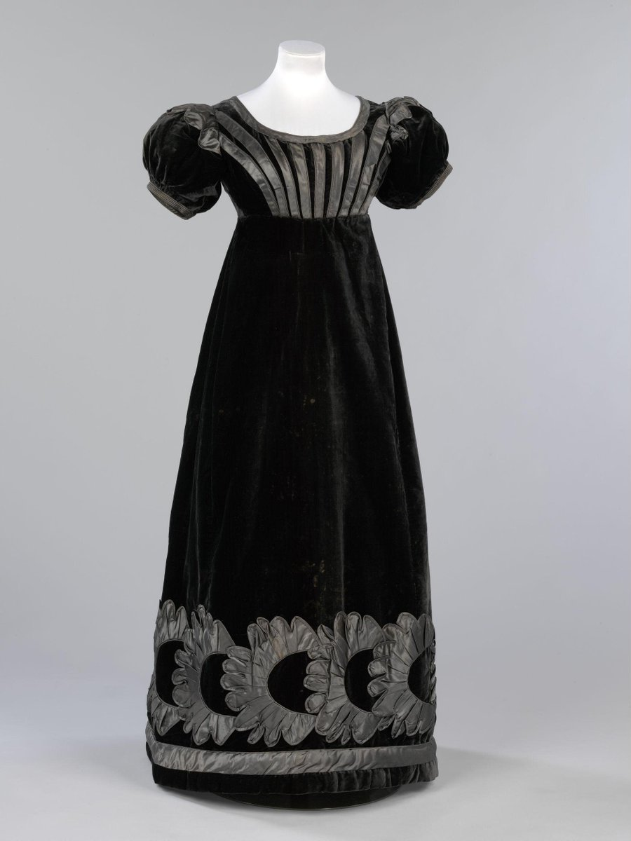 ©Victoria and Albert Museum, London - Formal mourning dress of black velvet and grey silk satin decorated with satin piping and appliqué. The dress is full length and has a wide, shallow neckline outlined with grey satin piping. It is lined with cream silk in the bodice and black silk grosgrain in the skirt. The short puff sleeves are decorated with an appliquéd satin motif stemming from the shoulder seams and are finished with the same satin piping. The waist is high but falls a good 5-10cm under the bust. Decorative lines of satin appliqué stem from the waistline to the neck and shoulder seams on the front of the dress and two lines of piping form a V shape from the waist to the shoulder seams on the back of the dress. The dress fastens at the back from the waist to the neck with seven hooks and eyes and a drawstring at the neck. The skirt is gored with a circumference of 220cm around the hem and is gathered slightly at the waist. The hem of the skirt is appliquéd with a wide band of