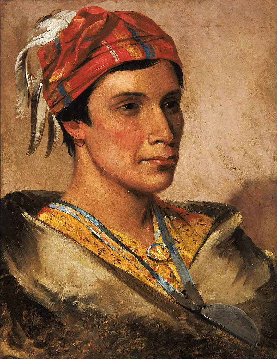 A man in a red hat, with feathers I white. He has black hair and black eyes, a yellow shirt, and a tan wrap around him. He is at 3/4 pose.