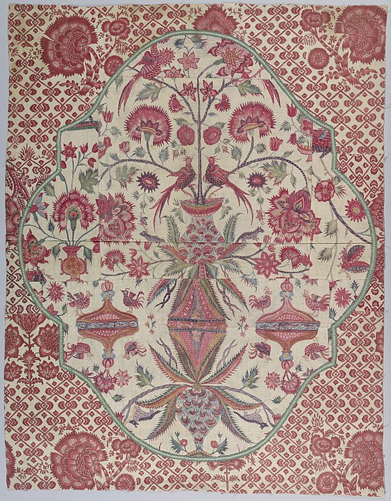 Shaped cartouche pieced from a palampore. Background of red and white chintz. Green and white braid applied to outline the edges of the shape. Public Domain.