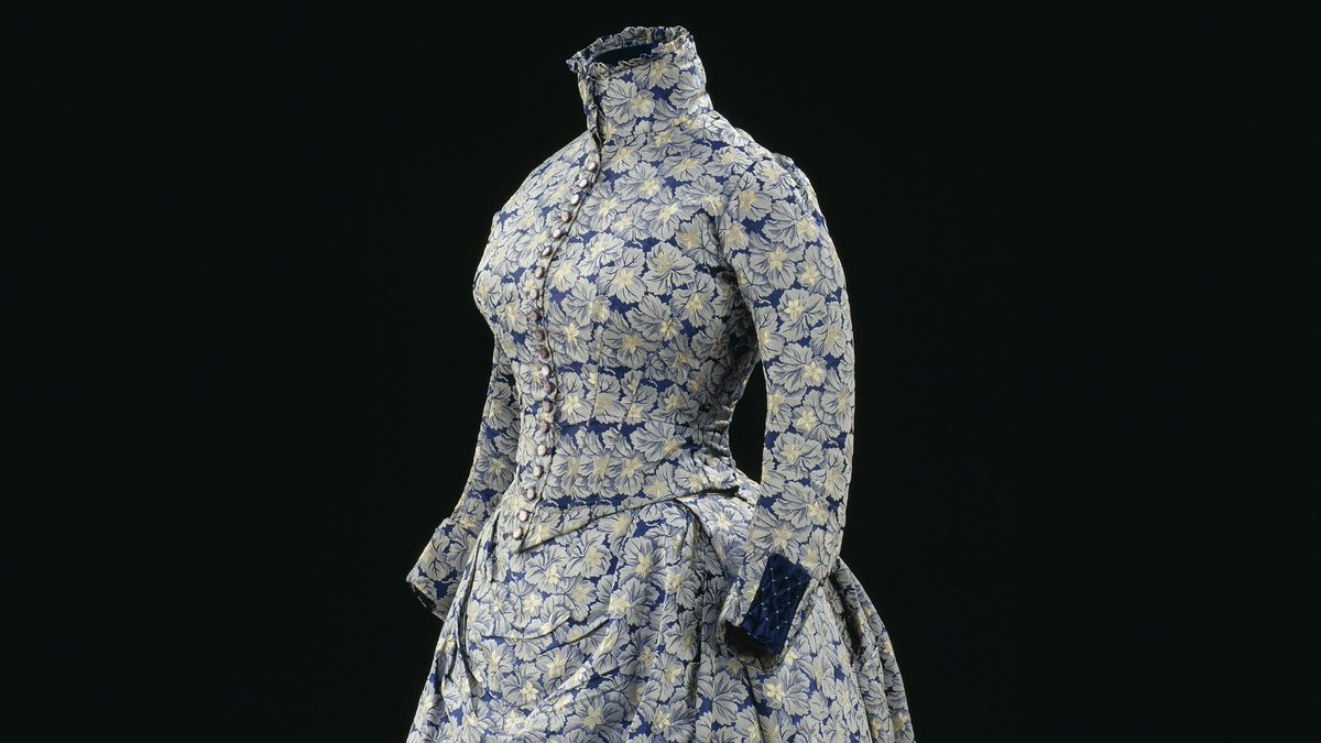 A Jacquard loom dress - 1885, Great Britain - a floral patterned walking dress with a high collar and dark blue background © Victoria and Albert Museum, London