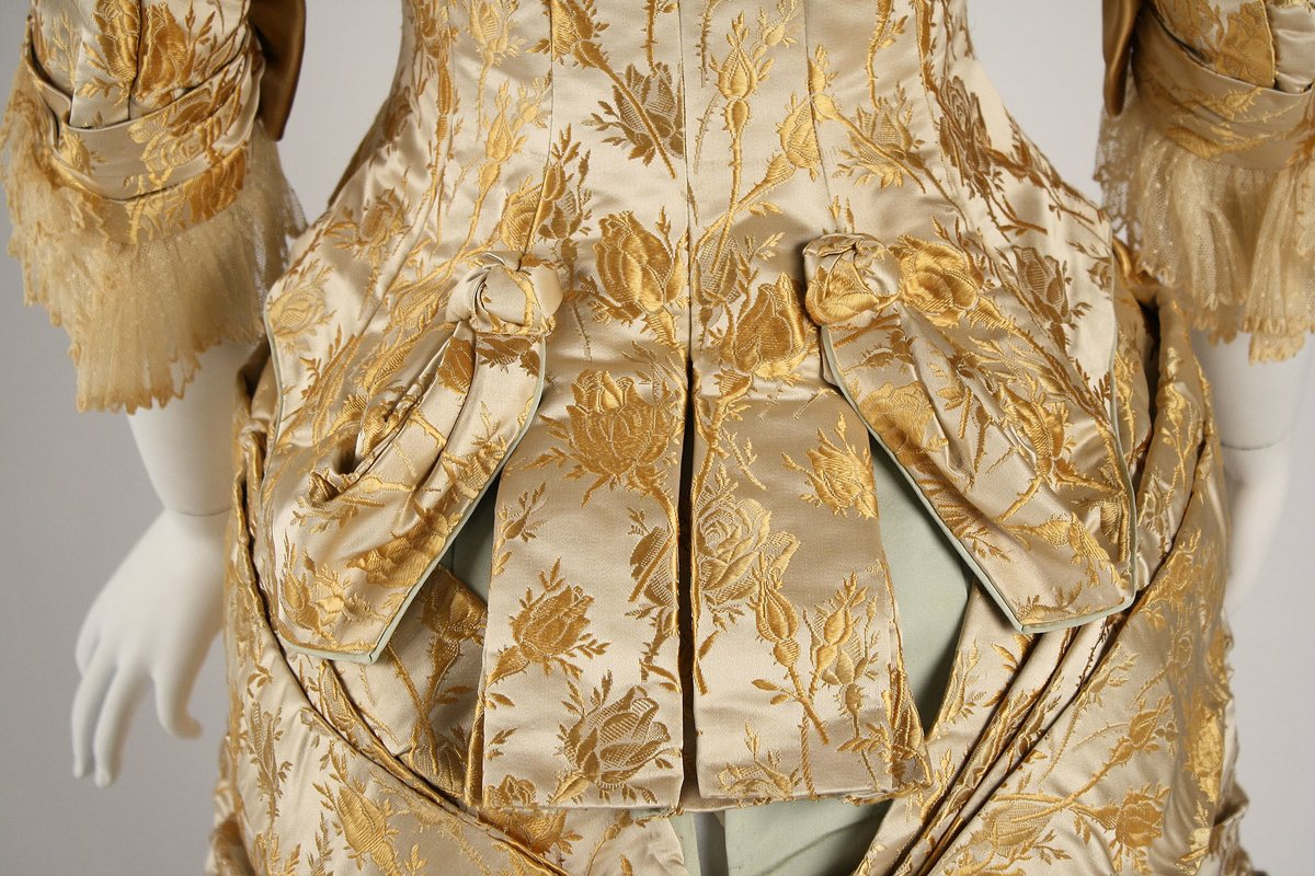 Dinner Dress - Evening Dress - ca. 1877 - House of Worth; a creme silk gown with fringe and significant damask print. Met Museum, public domain.