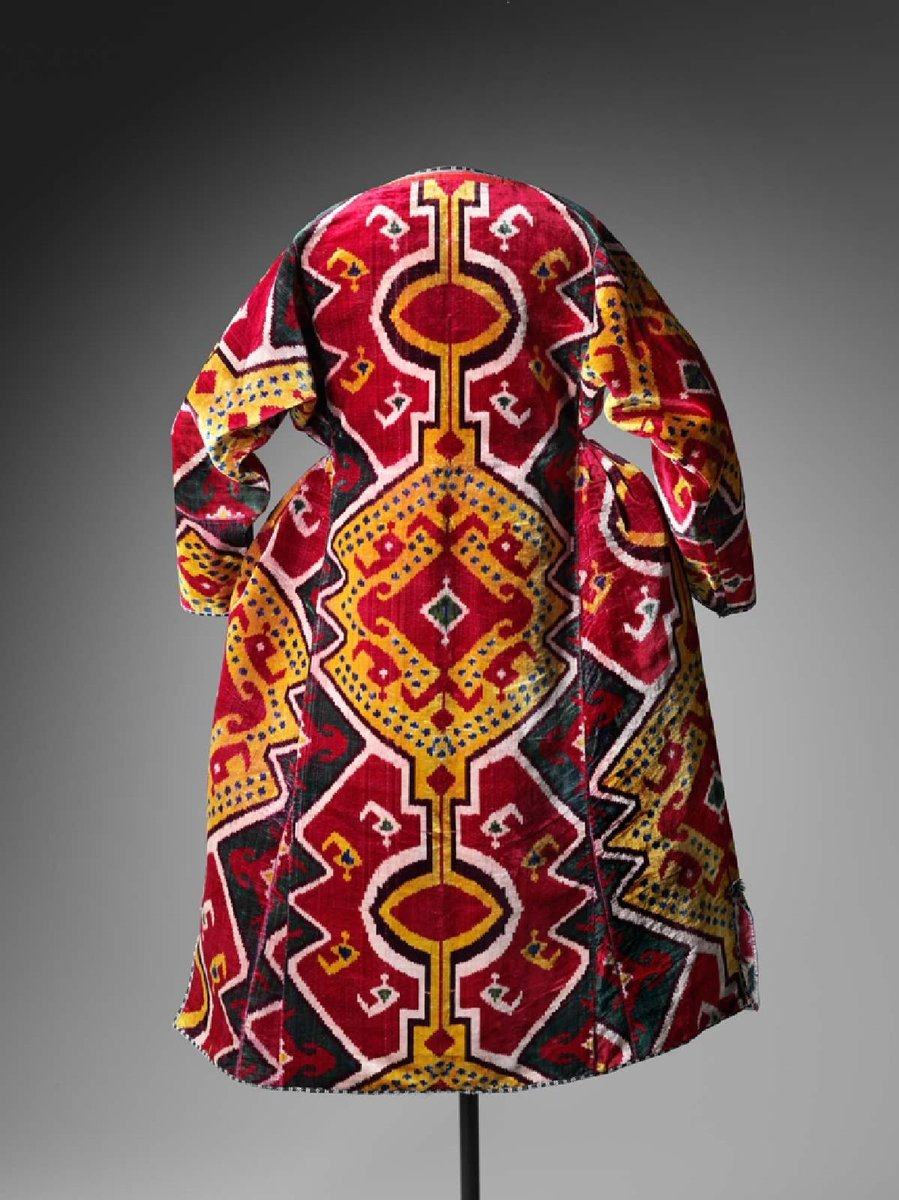 Woman's coat (chalat). Coat with flared hips and long tapered sleeves, open down entire front; skirt split at sides to just above hemline. Made of ikat velvet in bright, red, green, yellow, blue, violet and white. Lining shows border of glazed silk and cotton (weft) ikat in subdued tones of same colors. All edges trimmed with black, white and blue silks embroidered in herringbone stitch. White taffeta lining cracked, torn. - via Boston MFA