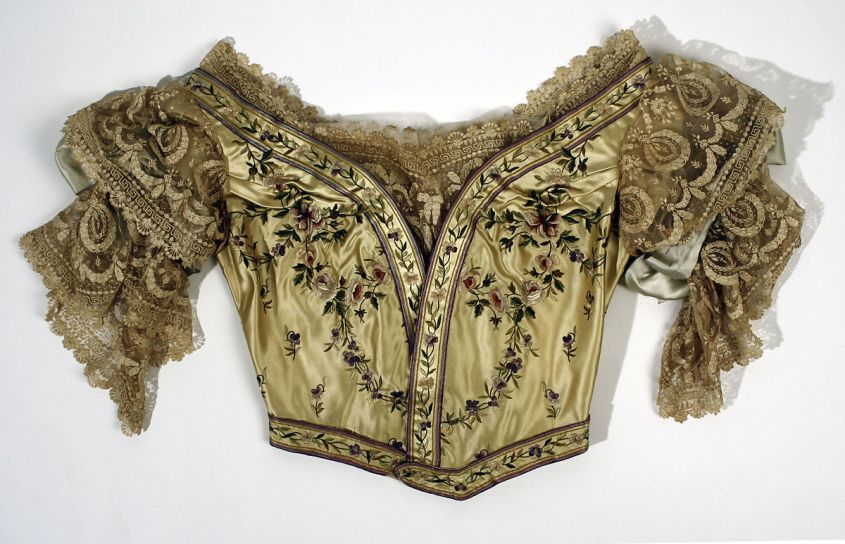 Neoclassical motifs on a silk embroidered bodice from the House of Worth, 1898. Ornate lace sleeves, yellow background, floral arrangements. From the Met Museum.