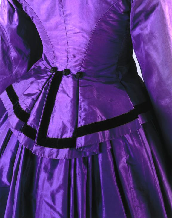 Vivid dress in satin with black piping at the bustle. Narrowed at the waist. Closeup of the back.  Science Museum Group Collection © The Board of Trustees of the Science Museum
