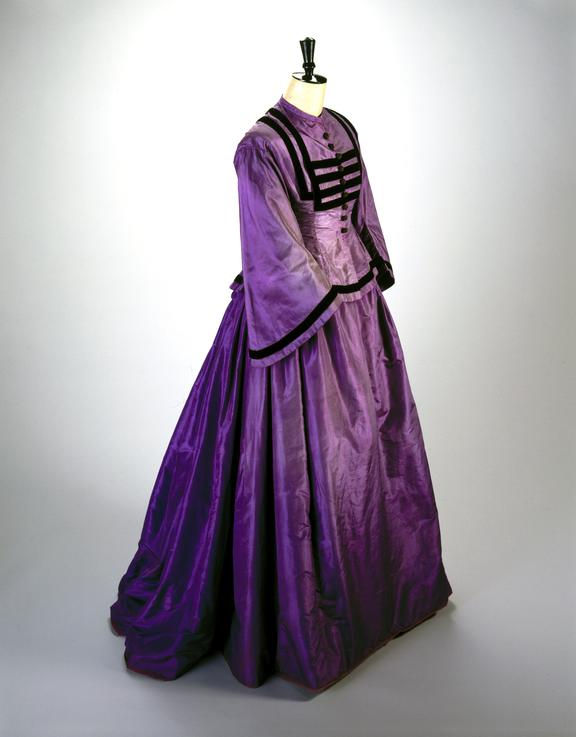 Vivid dress in satin with black piping at the bustle. Narrowed at the waist. Wide, flared sleeves. High collar, black buttons. Dating from the 1860s.  Science Museum Group Collection © The Board of Trustees of the Science Museum
