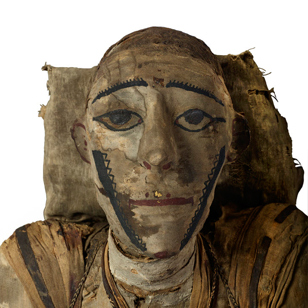 A male mummy, face wrapped and still preserved. Dark kohl on eyes, drawn eyebrows, and a mouth in red pigment. Ears also wrapped, and on a pillow. A rare Roman mummy of a 20+ year old man at the British Museum / British Museum