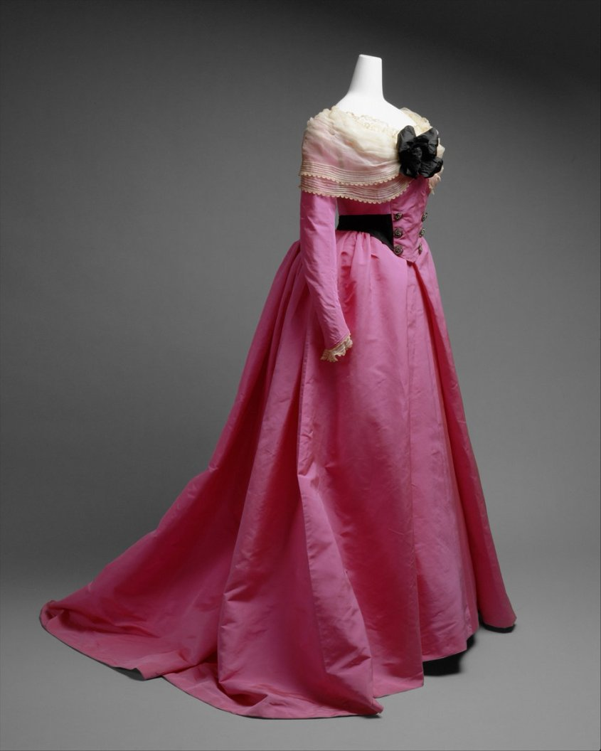 In addition to day and evening fashions for upper-class society women, Worth also created clothes for special occasions, such as the as-yet-to-be-identified fancy-dress ball to which this dress would have been worn. Composed of a separate bodice and skirt executed in shocking pink and black taffeta with paste buttons, machine lace trim, and pleated silk chiffon fichu, this gown illustrates the fashion for eighteenth-century revival, a popular theme for extravagant costume parties of the period. The narrow sleeves of the garment, along with the double-breasted masculine tailoring, imitation cut-steel buttons, lace fichu, and open front skirt, refer to fashionable women's styles of the 1770s. Public domain, Met Museum