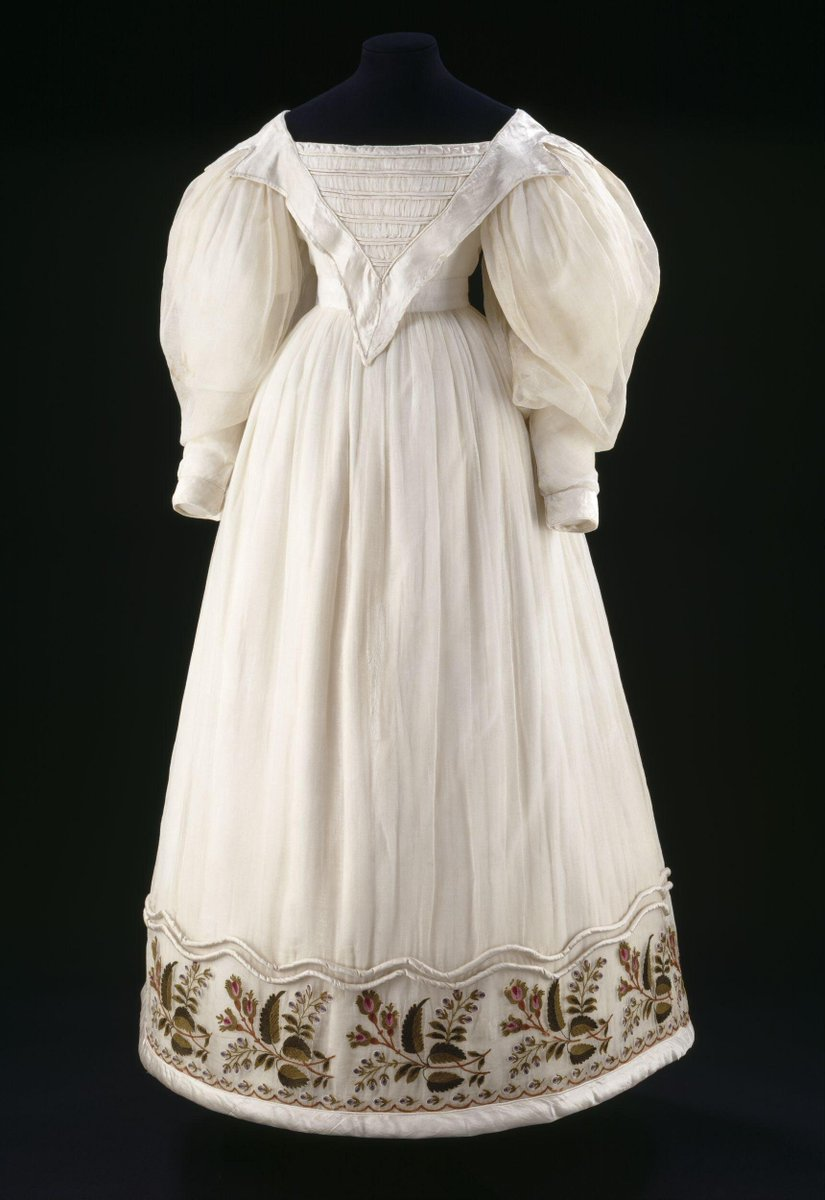 ©Victoria and Albert Museum, London - During the 1820s and 1830s women's dress took on a sense of romantic fantasy. Sleeves ballooned in shape, and skirts fanned out to emphasise a tiny waist. Hairstyles and headgear became equally exuberant, in contrast to the classical simplicity of the turn of the century. Decoration and trimmings reflected a nostalgia for the costume of the past, seen in stomacher-shaped bodices and 'vandyked' (zig-zag shaped) collars inspired by portraits from the seventeenth century.  This dress may well have been a wedding dress as it is so rich in detail and trimmings. White weddings were becoming widespread as a result of the fashion for muslin dresses. Before the 1800s most people wore coloured dresses to their marriage ceremony, which they continued to wear for special occasions long after the event.