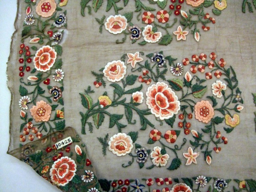 ©Victoria & Albert Museum, London - Length of unbleached muslin, with embroidered borders and ends in coloured, untwisted silks with flower and foliage design. Embroidery features three rows of flowers and leaves enclosed in buta patterns. Dhaka muslin from 1855.