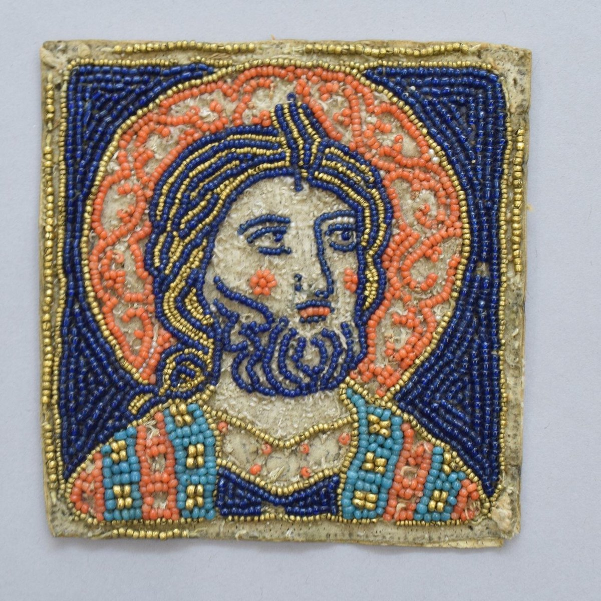 ©Victoria & Albert Museum, London - A 13th century square of a saint rendered in tiny seed glass beads. He is bearded with yellow hair and orange/red cheeks.
