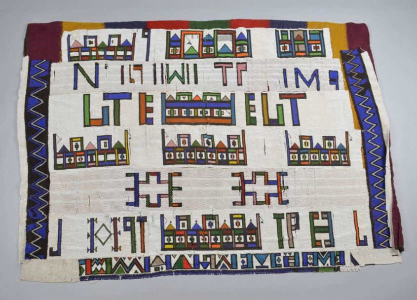 The British Museum, 2015,2011.1 - a large Ndebele blanket with writing and house-like geometric patterns made up of thousands upon thousands of beads -- colored mostly white, but also blue, green, orange, and yellow.