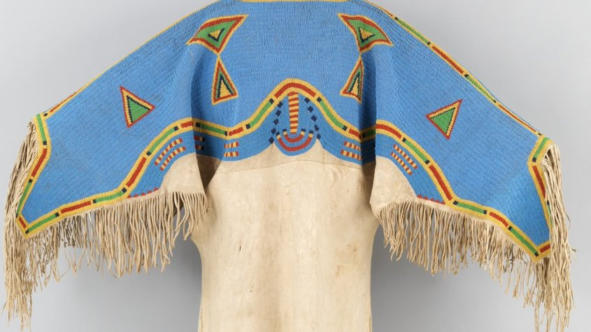 An intricate dress from the Sioux, ca. 1880 from the Met Museum (public domain). It is covered from the chest up in bright blue beads, adorned with geometric patterns in yellow, green, and red triangles, as well as semi-circles. The dress has fringe along the sleeves, and additional beads along the skirt.