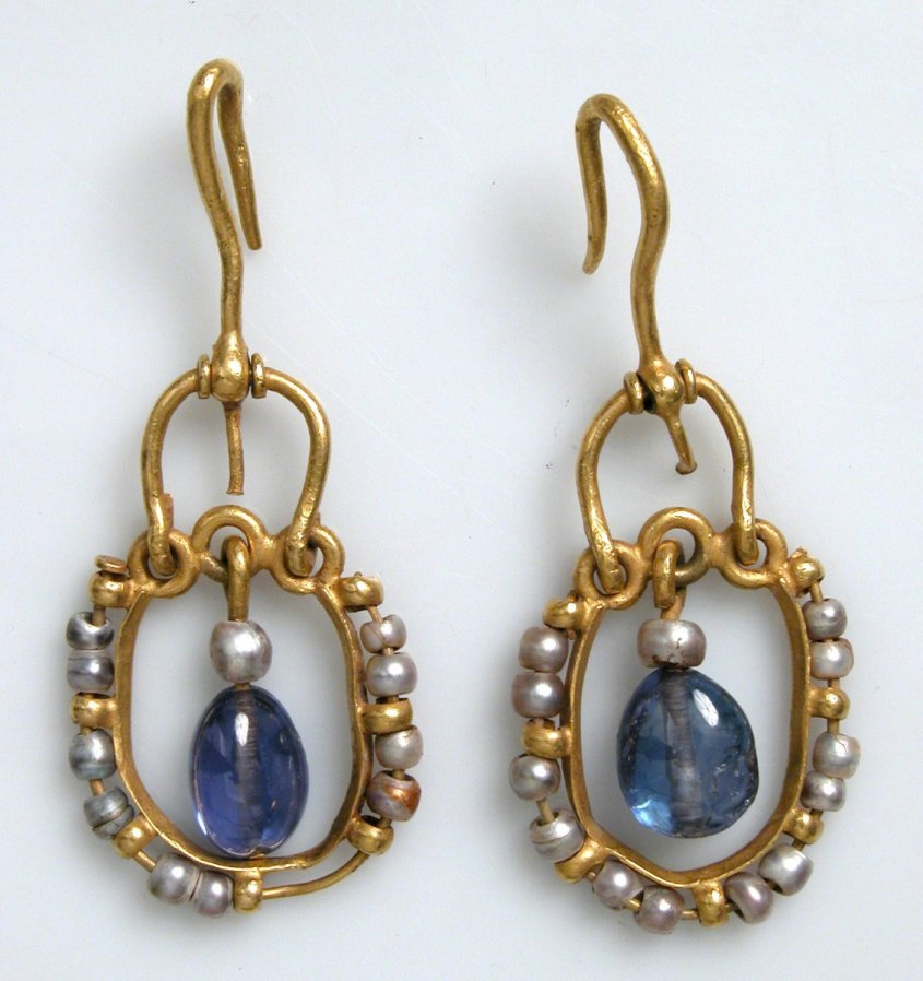 These elegant earrings are decorated with pearls, a favorite jewel of the Byzantines. Sapphires, then called hyakinthoi (hyacinths), became popular in Byzantine jewelry in the sixth century. They are made of gold wire and have grey pearls on the outside of an openwork ring; there are large sapphires in the middle.