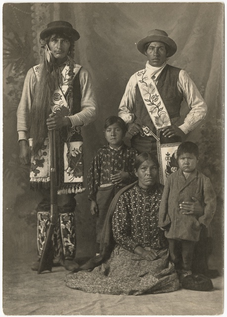 A family of five, including two small children. Many are dressed in highly beaded and embroidered outfits; both men are holding guns. It is in sepia color. From the Minnesota Historical Society.