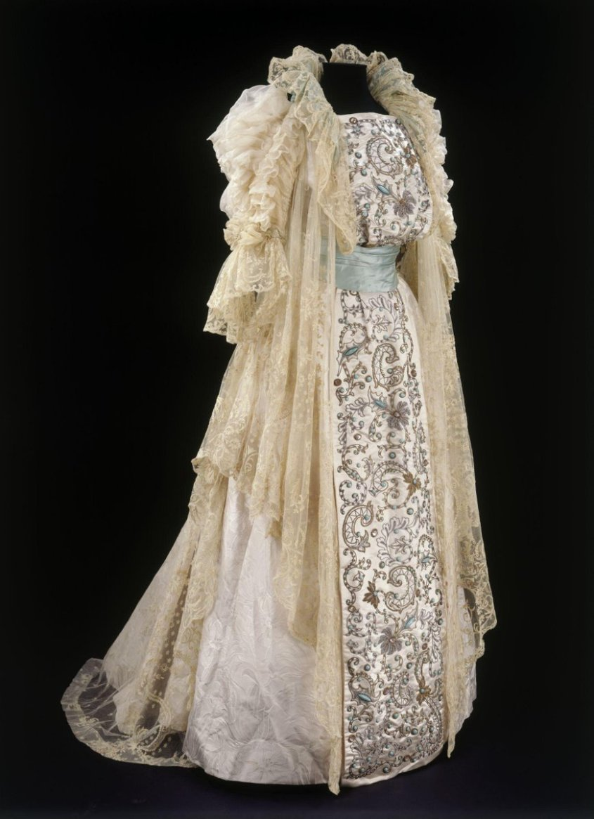 This example is very much a hybrid of influences and materials. The richly embroidered front panel of this gown was probably made in India but was designed to appeal to European taste, and it is complimented by the generous falls of Limerick lace. From the back, a long pleat of lace drops from the neck to the hem, a style known at the time as the Watteau pleat, after the dresses seen in paintings by the eighteenth-century painter. ©Victoria & Albert Museum, London