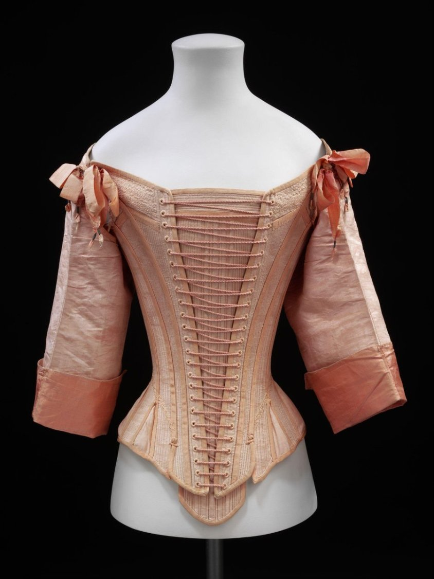 Front lacing stays and busk of pink watered silk, lined with linen and fully boned. All the outside edges of the stays are bound with pink silk grosgrain ribbon. The sleeves are made separately and laced into the armholes with pink silk ribbons and points of tinned iron. There is a band of back-stitched embroidery at the neckline and armholes and a line of couched thread at the waist. The separate busk is boned vertically and horizontally, at the top, and completely bound with pink silk grosgrain ribbon.  ©Victoria and Albert Museum, London