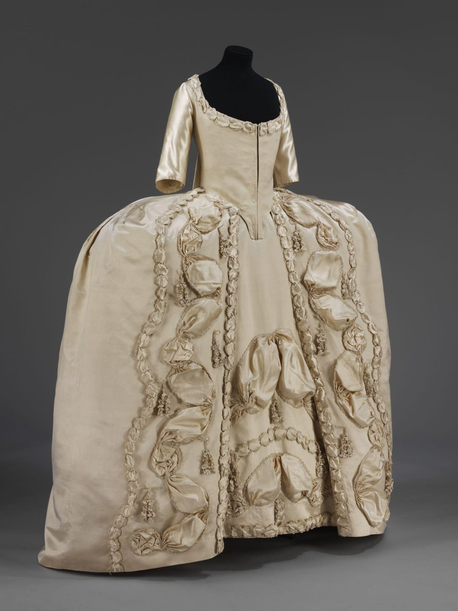 ©Victoria and Albert Museum, London - A woman's sack and petticoat of white silk satin. The sack is open at the front with elbow-length sleeves. The bodice meets at centre front, with boning on each side. The bodice and sleeves are lined with bleached linen. There is an opening at the centre back lining, boned on each side with lacing holes for adjusting the bodice. There are two, double, box pleats at the back, stitched at the neckline. The sack is made of 7 widths of silk, with a waist seam from the front edges to the side-back seam. The skirts are shaped for a wide hoop. The hem is faced with a deep band of white silk taffeta. The skirt fronts are decorated with a wide ruching of satin, edged with white silk chenille fringe, gathered into puffs and arranged in at zig zag pattern, and passementerie tassels of white silk chenille. Narrower ruchings of silk and chenille are placed either side of it. The same narrow ruching adorns the neck.
