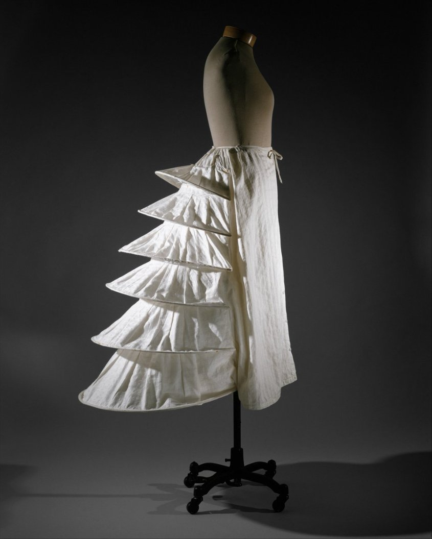 This 1871 bustle is made of metal wire fully encased in cotton fabric. Of the means employed to force the projecting hoops toward the back of the body, the most common were interior fabric tapes or a panel that lay against the back of the body. This solution was not unlike that used to create eighteenth-century panniers. - Met museum