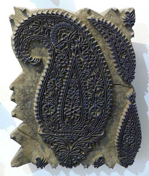 An ornate carved stamp of a complex boteh pattern, used for printing cotton. There are additional motifs inside the larger motif, too. You can still see the dark blue ink on the woodblock. Image via Wikipedia.