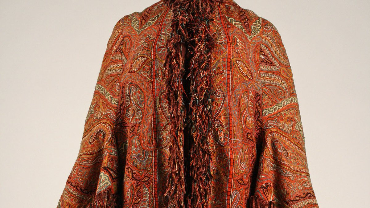Visiting Cape - the Met. Mid-1960s. A vivid red, orange, yellow, and brown paisley jacket with long, bell sleeves and fringe all along the cuffs, bottom, collar, and button area. Public Domain.