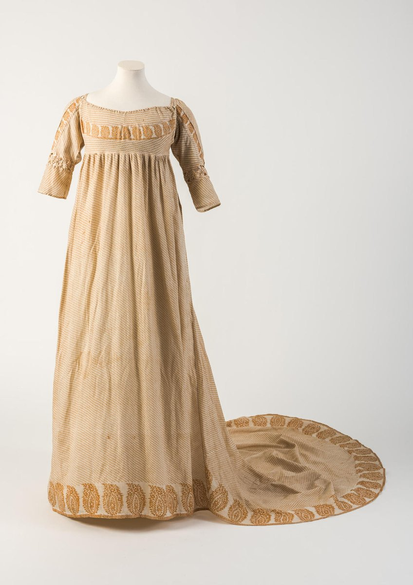 Orange/yellow printed cotton gown, with pine cone or patka motif, 1800  - From the Costume Museum of Bath. The dress has 3/4 sleeves and bokeh patterns around the bust, down the sleeves, and at the hem.