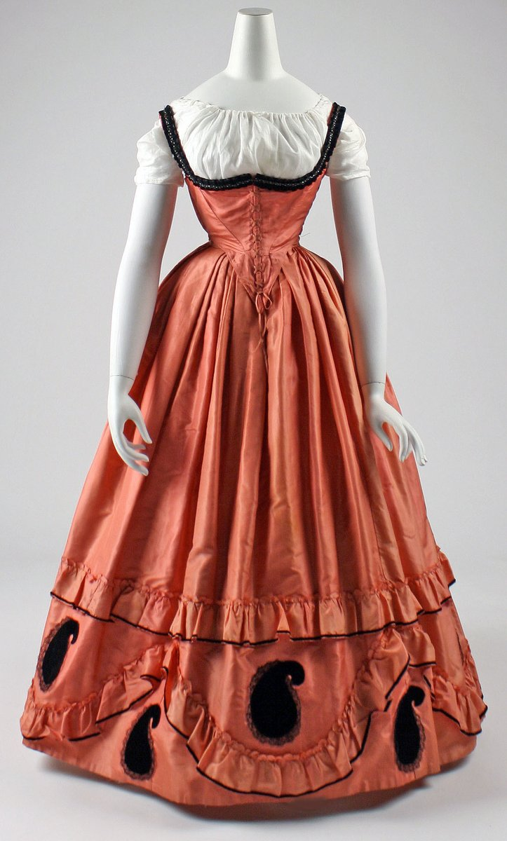 A gown in coral red with paisleys at the bottom in black velvet. The top is a narrow waist and undercuts design with a white shirt below. Met Museum, public domain.
