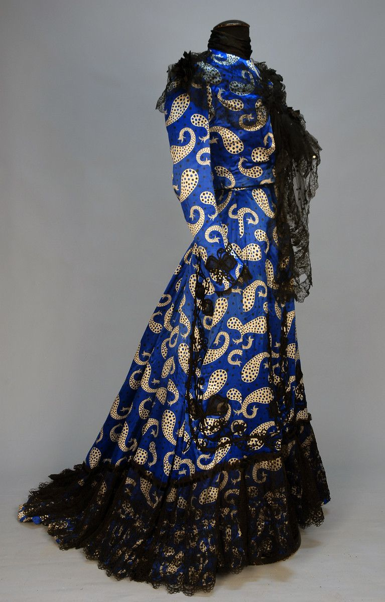 2-piece black dotted sapphire blue silk with white paisleys of varying sizes having black and blue dots, boned bodice trimmed in black embroidered net with sequins and bowknot appliques on sleeve, skirt having appliques, ruffled hem with non-conforming lace over ruffle, cotton lining. Whittaker auctions.