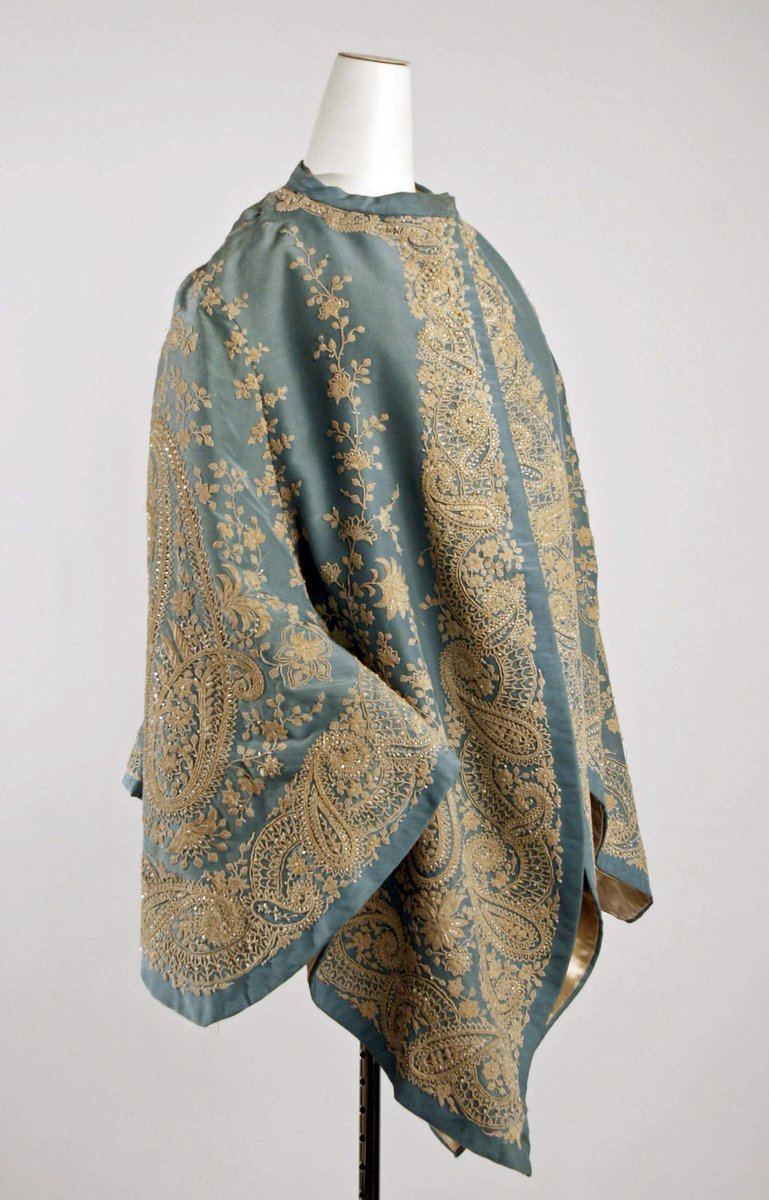 A silk, sky blue mantle with elaborate paisley embroidery around the cuffs and sleeves, beaded and lined with gold satin. Met museum, public domain.