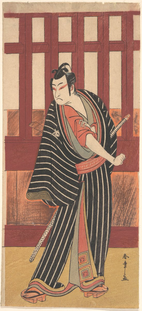 A man in Japanese theatre costume with a long kimono in black wide stripes with narrow white stripes. Below he wears a red tunic. He has red makeup on his eyes and is scowling, a sword at his side. Met Museum, Public Domain.